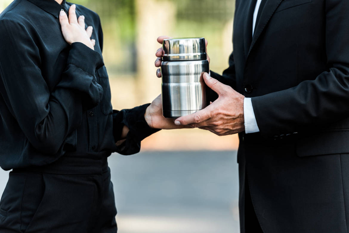 cropped-view-of-man-and-woman-holding-mortuary-urn-YY58W9Q-1-scaled.jpg